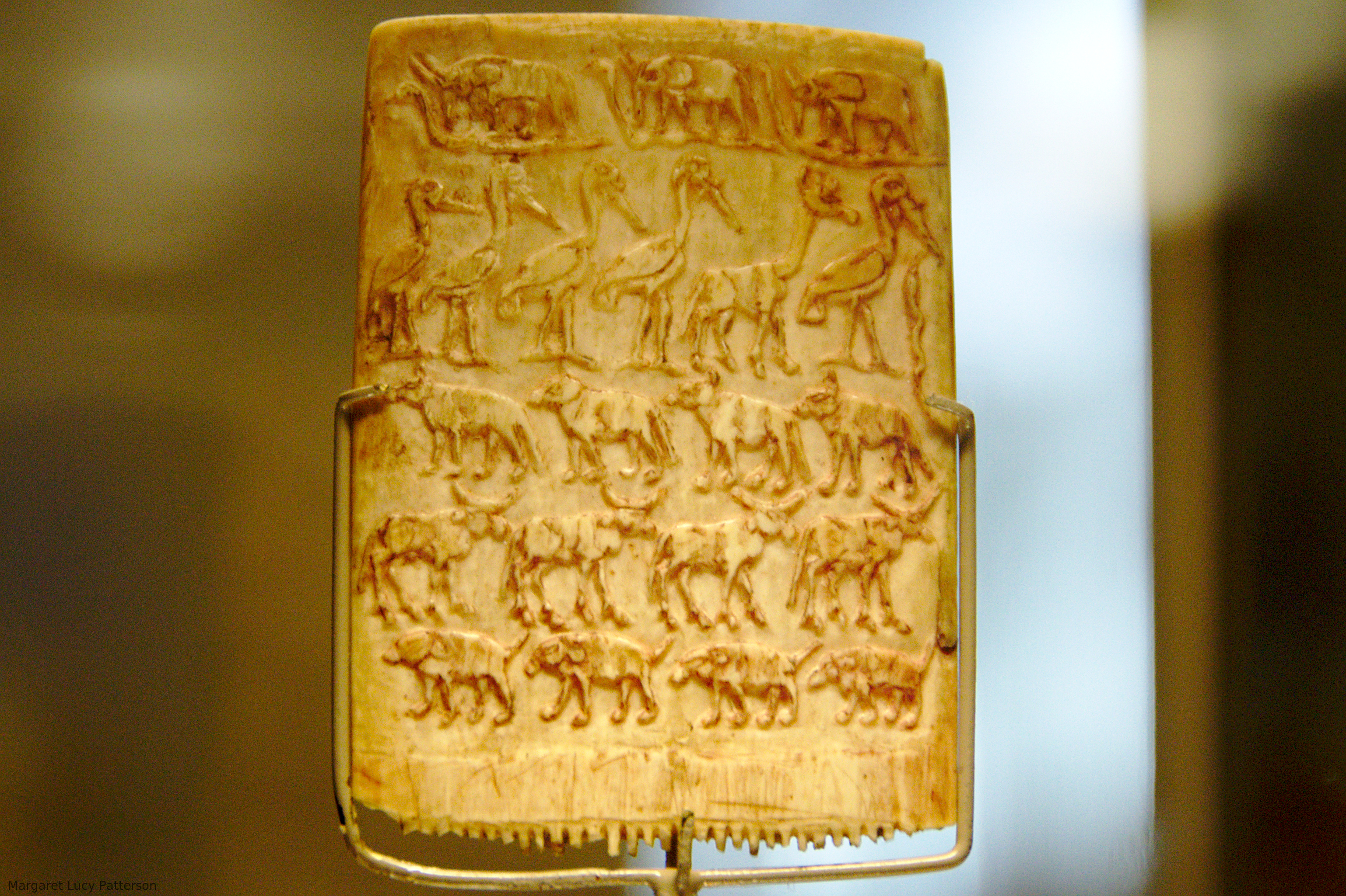 A Predynastic ornamental comb carved with rows of animals, including a row of long legged birds which includes a giraffe.